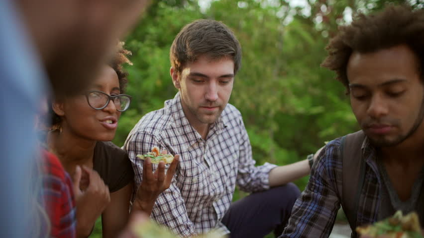 Close up view of five interracial friends sitting in park eating pizza talking smiling discussing in slowmotion | Shutterstock HD Video #23236321