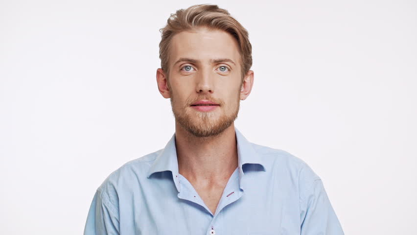 Surprised young bearded Caucasian male with blue eyes and brown hair looking at camera with amazement on white background slowmotion
