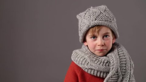 cute 6-year old boy with freckles wearing warm winter scarf and hat  thinking 576f3059f64e