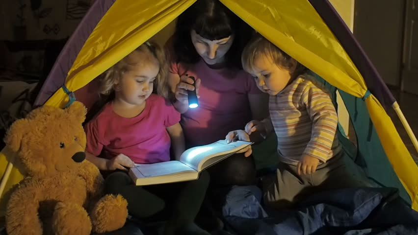 Little boys and girl with flashlight reading book at night in teepee happy family is reading a book with flashlights in tent mother with her daughter and sciox Gallery