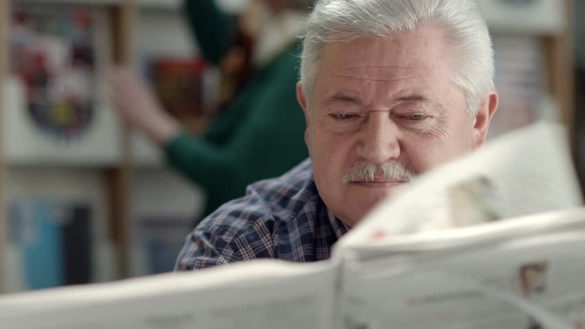 Active retirement, senior man with mustache reading newspaper in library