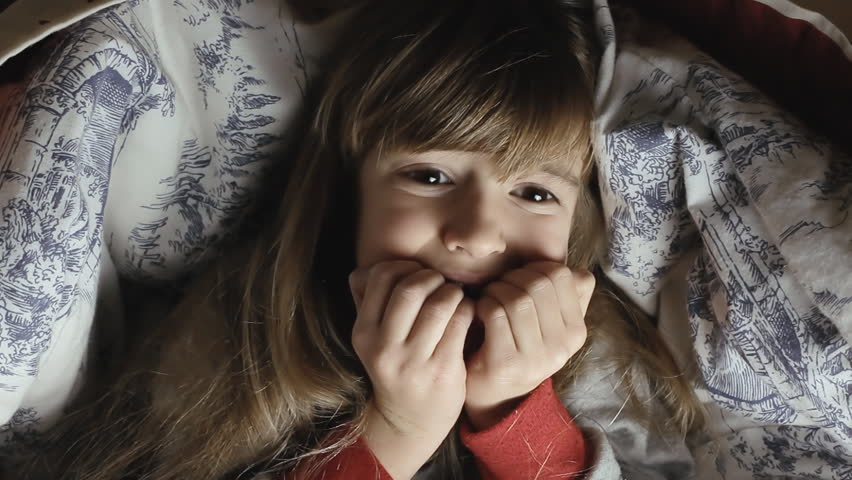 A little girl lying in her bed, under the sheets, at night. She is alarmed and scared.