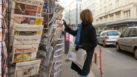 PARIS, FRANCE - JAN 21, 2017: Woman purchases a L'Alsace French newspaper from a newsstand featuring headlines with Donald Trump inauguration 45th President of the United States in Washington, D.C