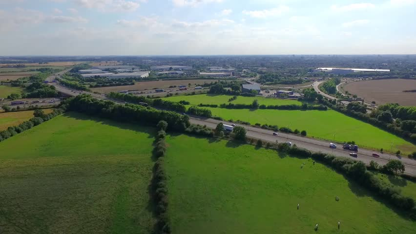 Flying over lush green fields towards the City of Coventry and it's ring road, aerial drone footage 50fps
