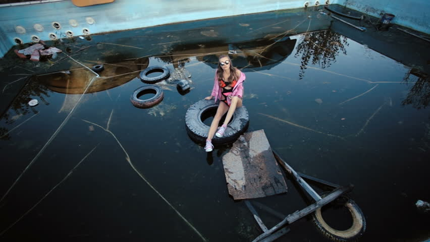 Beautiful young girl with glasses posing in an abandoned pool at summer evening