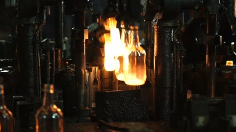 Production of glass bottles. Glass recycling. Bottle manufacturing industrial factory. Molten glass. Glass factory. Automated production line. Furnace. Recycling. Special equipment.