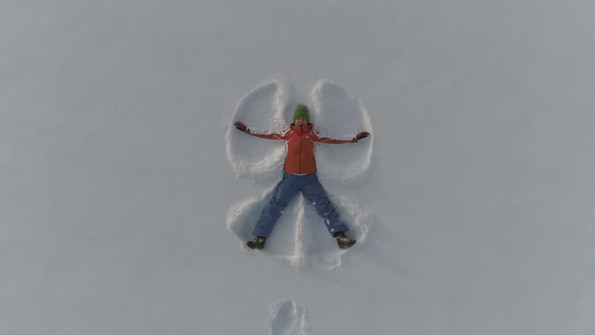 Woman making snow angels and playing in snow. Aeriel view from the drone