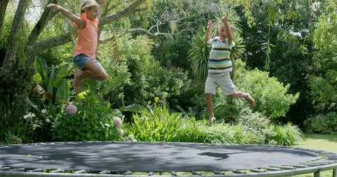Brother and sister jumping on trampoline in slow motion in the garden