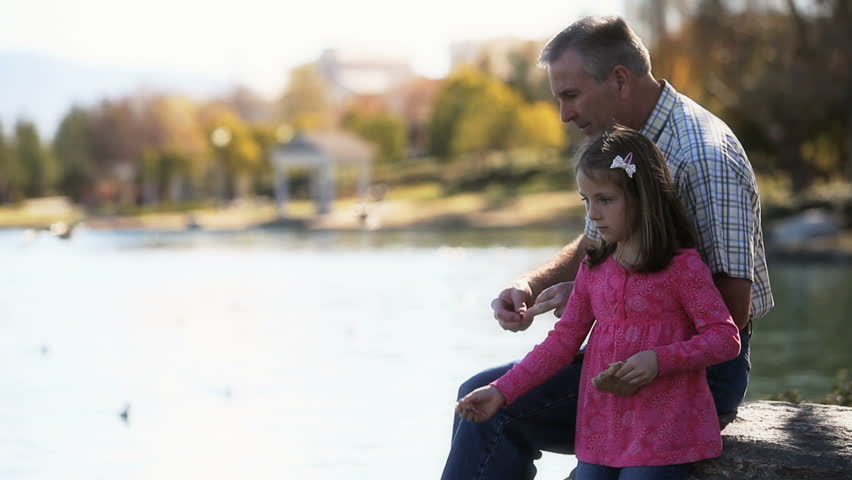 Father and daughter feeding ducks