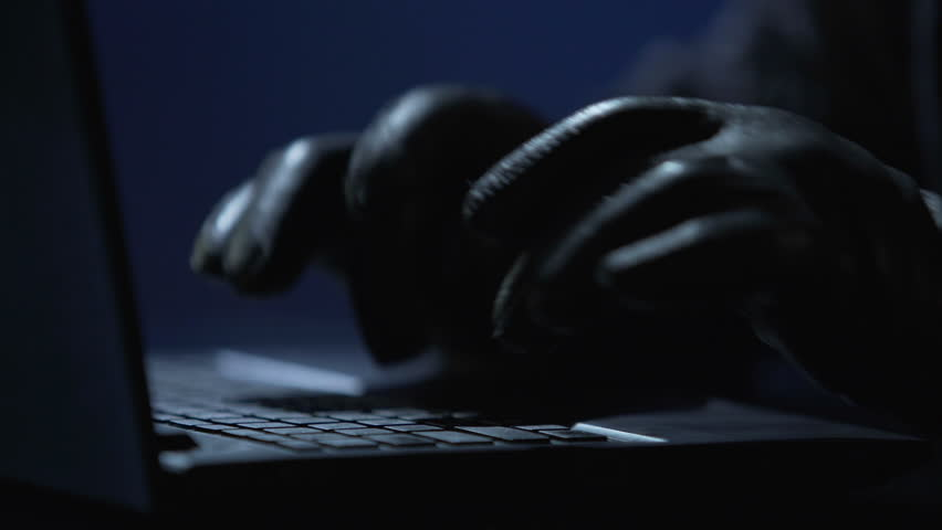 Hands of computer hacker in black gloves typing on laptop to hack banking system