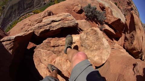 Perspective Shot of Hiker's Legs as he Hikes on Desert Cliff