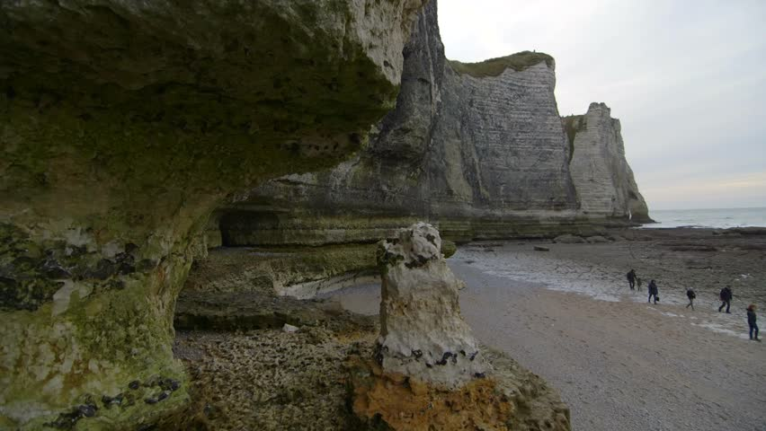 People inspect nude beach at low tide. Cloudy winter day in Etretat. France