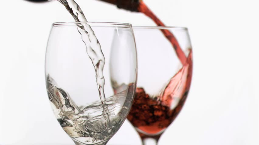 Glasses of wine in super slow motion being filled against a white background