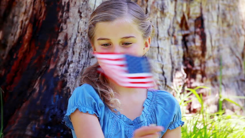 Girl playing with an american flag in a park