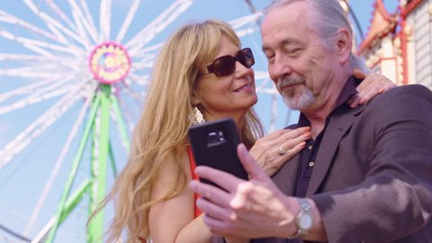 Older couple in love take self portrait on a mobile phone at an amusement park