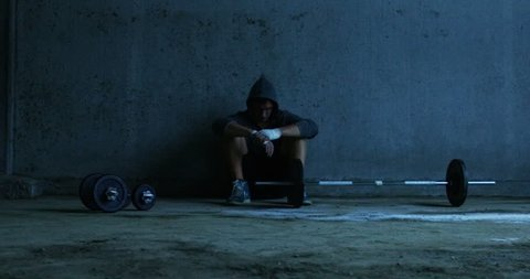 A man in an old gym with soft light, prepares training and effort to lift weights. Concept: ambition, dreams, passion, sports, lifting weights.