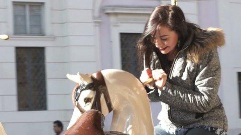 carefree woman has fun on the carousel