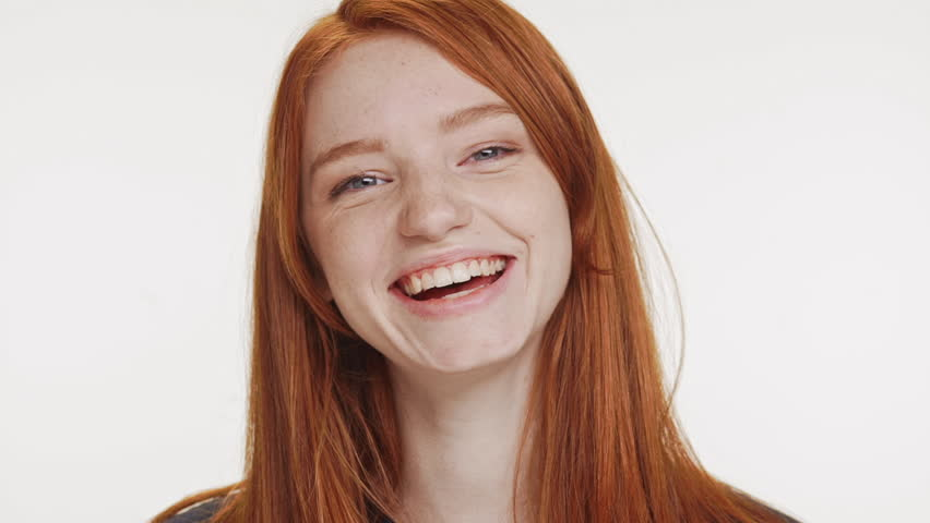 Close footage of young Caucasian red haired teenage girl smiling laughing on white background in slowmotion