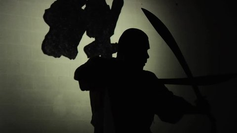 A Shaolin monk demonstrates in silhouette his ancient form of kung fu using two swords. Shot in slow motion.
