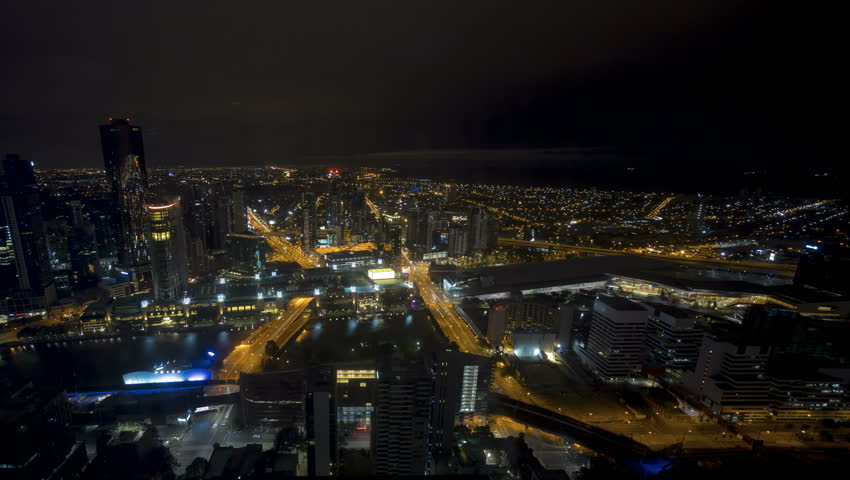 An aerial view of Melbourne cityscape including Yarra River and Victoria Harbour in the distance. Time lapse during sunrise night to day sky with fast moving clouds. Pan left | Shutterstock HD Video #23478751