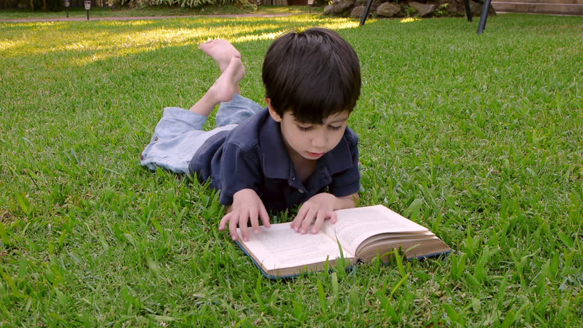 Kid Reading Book (HD)  Four year old boy of Hispanic origin flipping the pages of a book lying on a grassy patch.