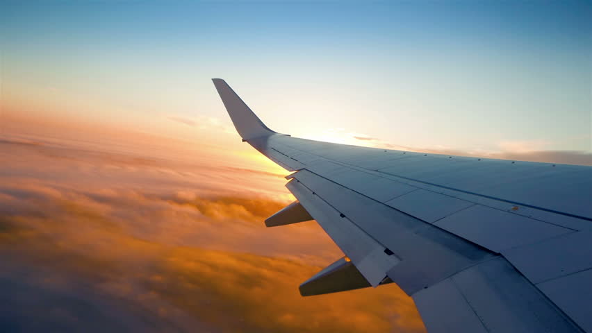 Plane flight above the clouds, sun glimpse over wing | Shutterstock HD Video #23524987
