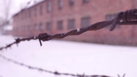 Close-up shot of old rusty barbed wire fence in former concentration camp. Brick barracks in the snow. 4K clip