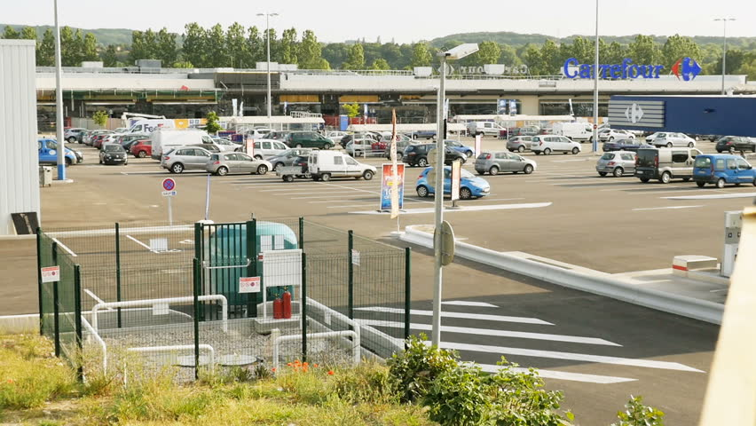 L'Isle-d'Abeau, France - Circa 2017: Carrefour hypermarket supermarket parking with cars driving toward exit and customers. It is one of the largest hypermarket chains in the world