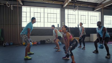 Group kettlebell exercises with trainer, strength training endurance workout