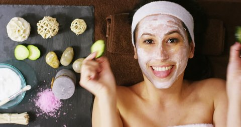 top view of young woman with facial mask and cucumber treatment on her face have a relax in a wellness center. Concept of skincare, cosmetics, beauty salon, facial treatment, facial massage, wellbeing