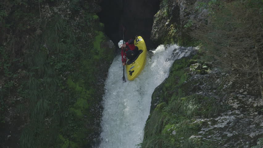 SLOW MOTION, CLOSE UP: Extreme pro canoer soaring above raging whitewater river washing rocky mountain ledge. Adrenaline rushing through man descending on the rapids and paddling through big waterfall