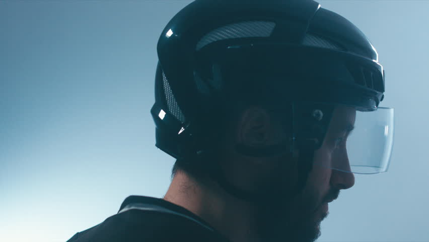 CU Portrait of Caucasian male ice hockey player in black uniform putting on his protective helmet in locker room. 4K UHD 60 FPS slow motion. RAW edited footage