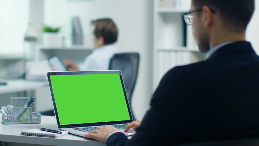 Young Businessman Working on His Laptop with Green Screen. His Colleague Sits at His Desk Using Tablet Computer. Shot in a Modern and Light Office. Shot on RED Cinema Camera 4K (UHD). | Shutterstock HD Video #23570881