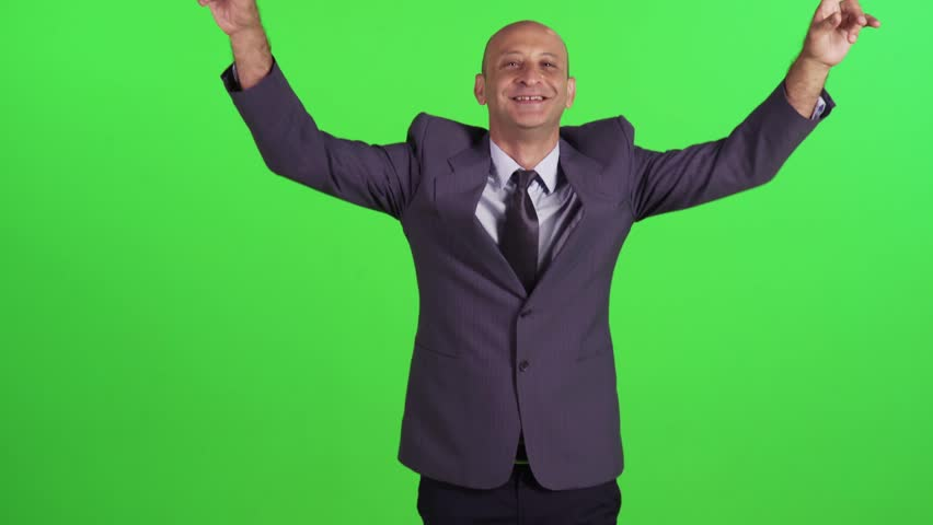 Extremely happy businessman goofs around while walking towards camera, wearing a suit. Medium frontal shot over a green screen. | Shutterstock HD Video #23578111