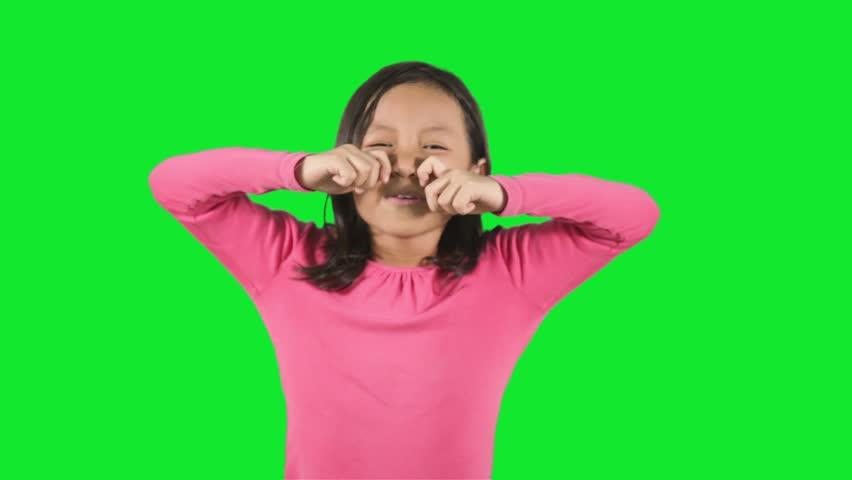 Expressive little girl crying while standing in the studio with green background. Shot over green screen.  | Shutterstock HD Video #23614351