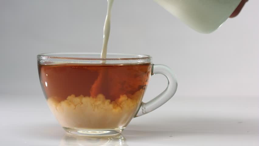 black milk tea adding milk to black tea in a glass mug extreme close up stock