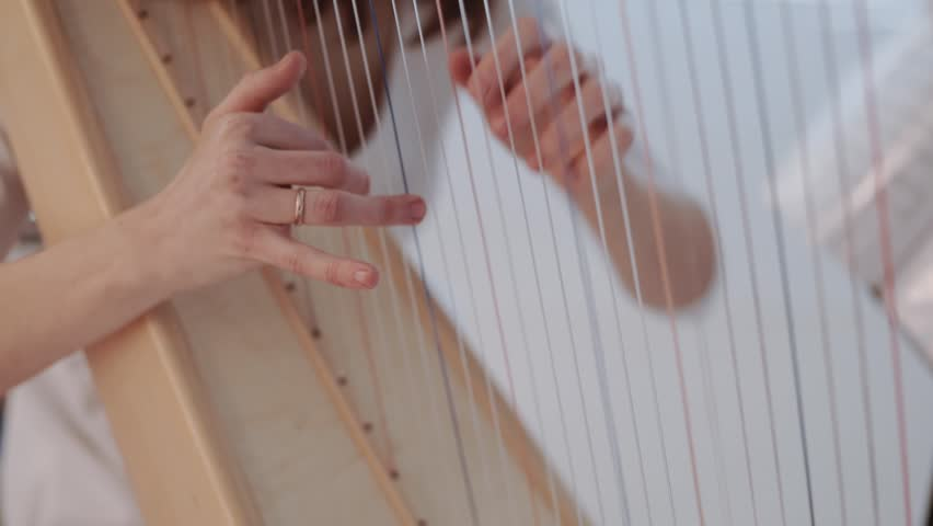 Hands of woman playing a harp. Harpist with classical music instrument. Harp strings close up.