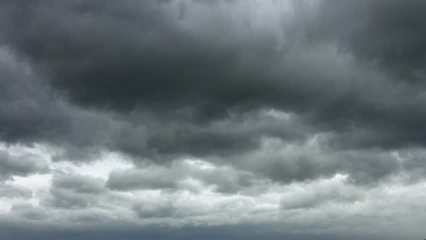 Heavy and ominous. dark gray clouds drift slowly across the sky. threatening rain. UltraHd 4k video