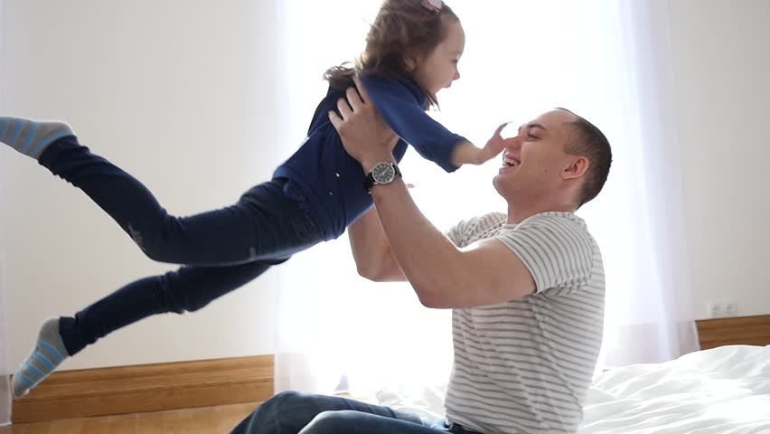 Happy Family Idyll Little Child Daughter Jump On Father Arms And They Fall On A Bed | Shutterstock HD Video #23641642