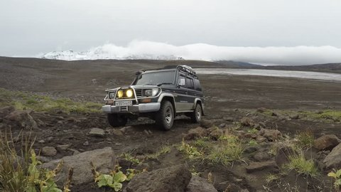 KAMCHATKA PENINSULA, RUSSIA - SEP 17, 2016: Extreme off-road expedition car - Toyota Land Cruiser Prado (70 series) driving on rocky mountain road on background of volcanic landscape in cloudy weather