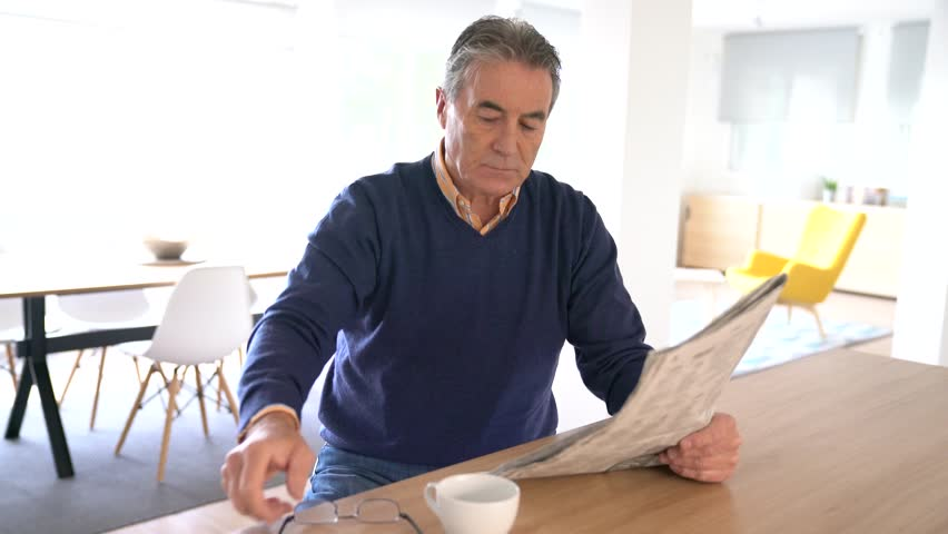 Smiling senior man with eyeglasses reading newspaper