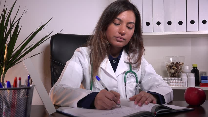 Attractive Woman Doctor Writing Prescription In Office Medical ...