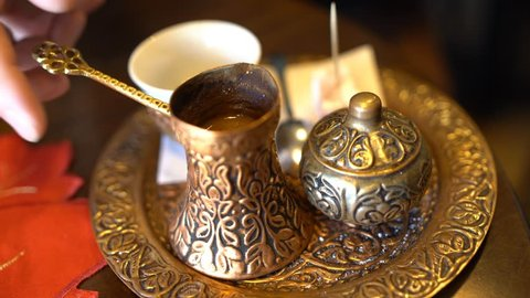 Close up shot of a strong black coffee being poured from brass pot in a traditional Ottoman styled brass coffee set.