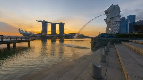 Beautiful and clear night to day time lapse of Singapore cityscape with the Merlion statue during sunrise at Marina bay quay, Singapore. 4K UHD, Motion Timelapse Slow Slide from Left to Right