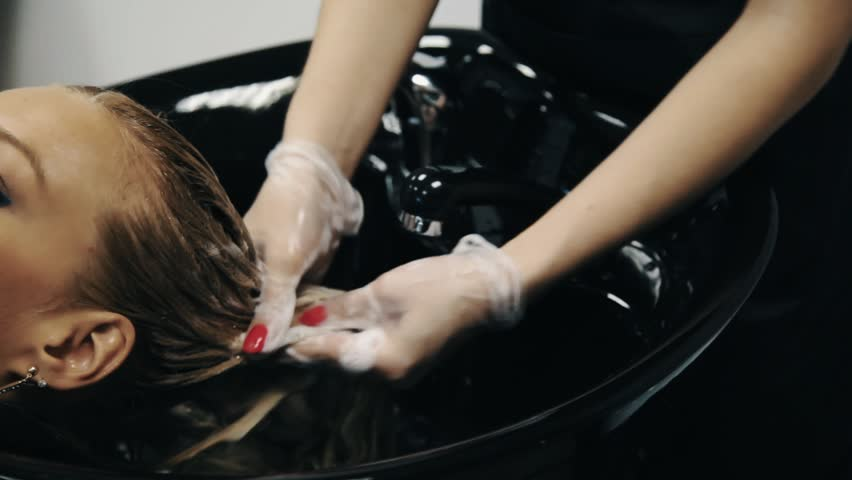 Hair Stylist In Gloves Washing Blond Dyed Girl Head Over Sink In ...