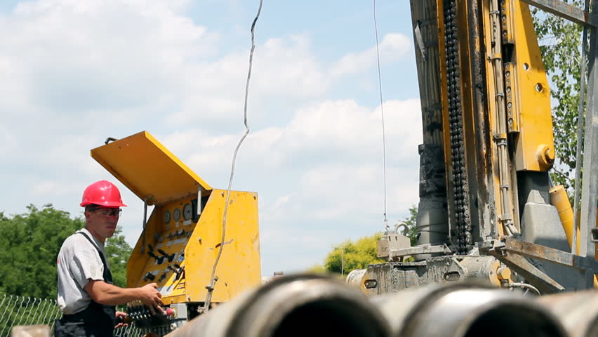 Oil drilling rig workers lifting drill pipe. HD1080p.