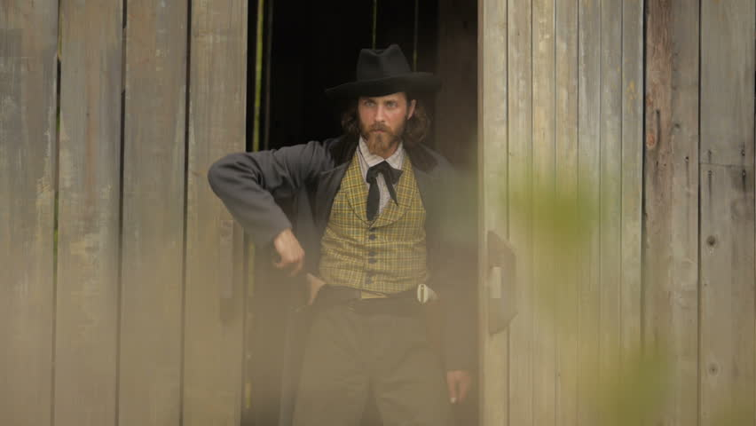 VIRGINIA - 2014. Re-enactment recreation of classic Old West, 1800s Western gunfight, and Killing. Cowboys and Outlaws. 1870-1890 western life. Guns and shootouts. OK Corral. Tombstone. Guns fire.