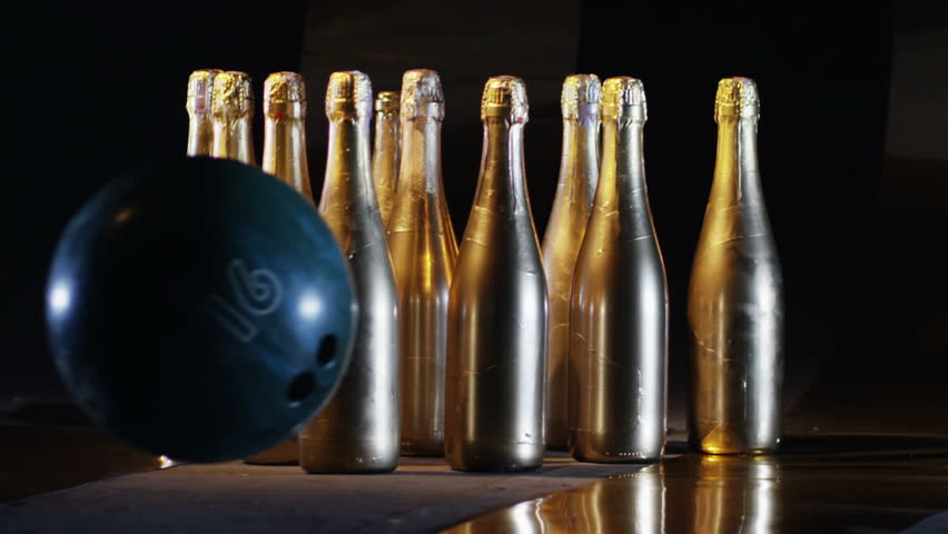 Bowling ball rolling and braking the golden bottles of champagne, puted like ninepins. Shot on RED HELIUM Cinema Camera in slow motion 250fps.