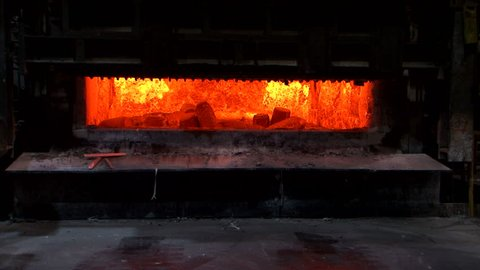 Aluminium foundry furnace loaded with metal. red hot flames glowing. liquid melting