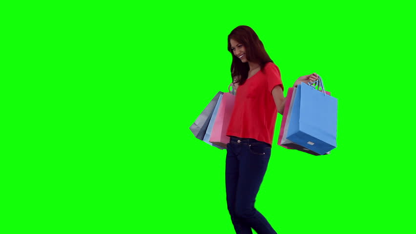 Woman dancing while holding shopping bags against a green background